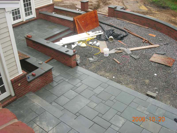 Exceptional Upper Patio Is Paved   Over Concrete Base   With Bluestone Slate. Future  Raised Flower Beds Are Established Behind The Brick Wall Capped With Slate.